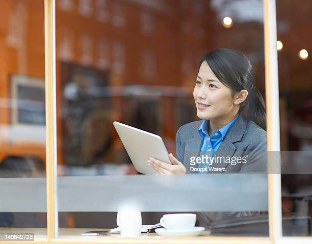 Business woman in cafe using digital tablet.