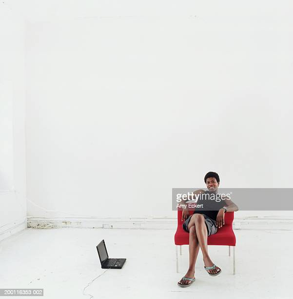 Business woman in chair with laptop on floor, portrait