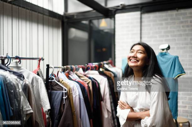 Business woman in front of a clothing rack in a boutique