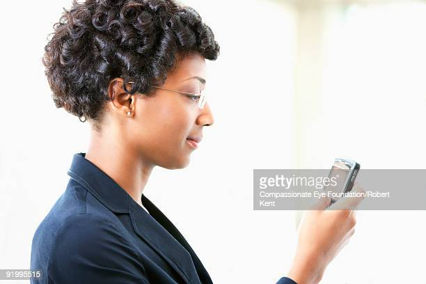 business woman in glasses looking at cell phone