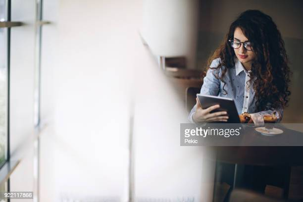 business woman in local cafe checking social networks - job search stock pictures, royalty-free photos & images