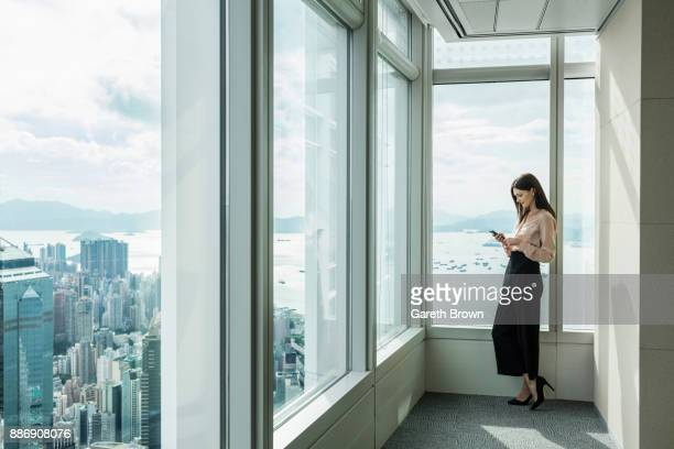 business woman in skyscraper office window using smartphone - fashion hong kong stock photos and pictures