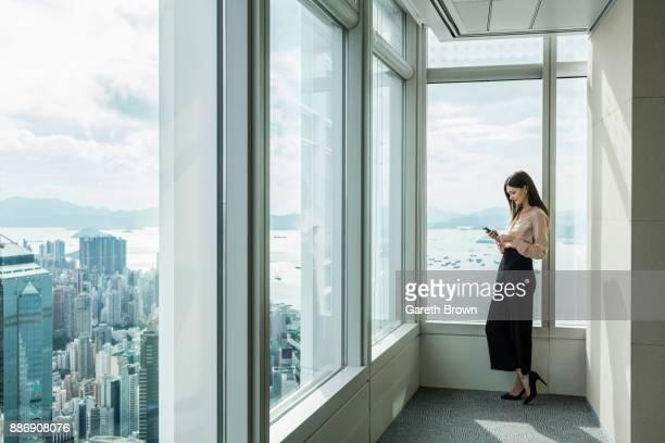 business woman in skyscraper office window using smartphone - eleganz stock-fotos und bilder