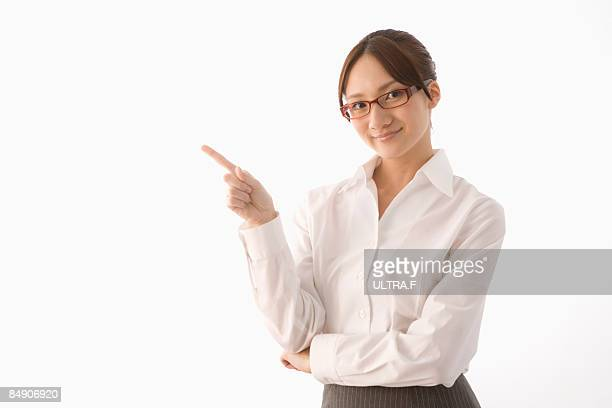 A business woman is pointing her forefinger.