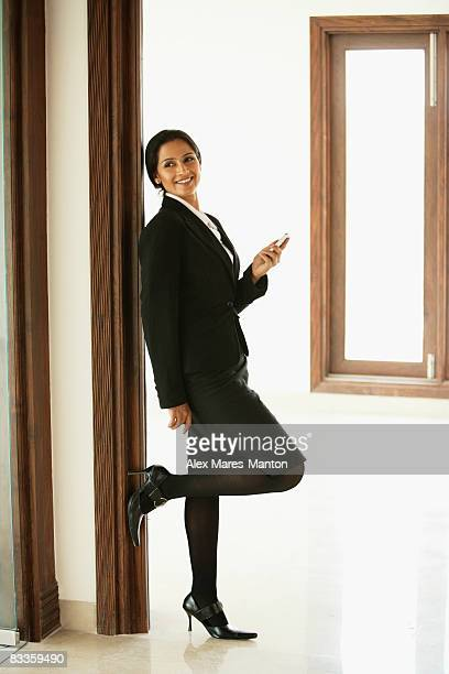 business woman leaning against wall, mobile phone in hand