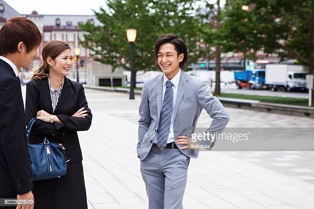 Business woman listening to colleagues talking while building arms