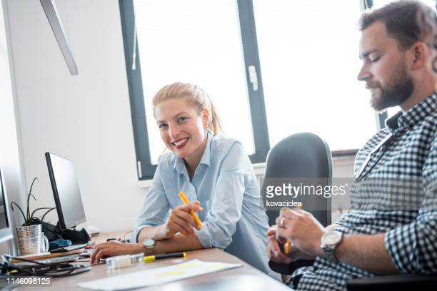 business woman looking at camera and working with her colleagues in the office and brainstorming - mid adult men stock pictures, royalty-free photos & images