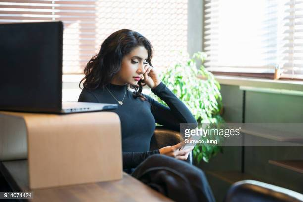 Business woman looking at smartphone in modern office