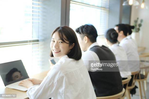 Business woman looking back by operating a laptop computer
