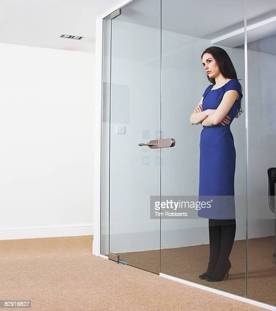 Business woman looking out of office meeting room