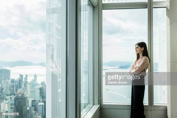 business woman looking out of window at cityscape - fashion hong kong stock photos and pictures