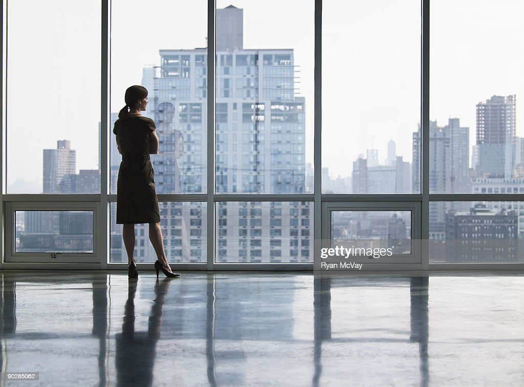 Business woman looking out window : Stock Photo