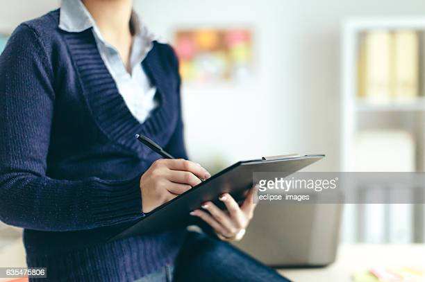 business woman looking over papers - petition stock photos and pictures