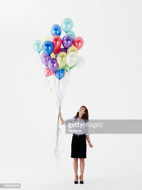 Business woman looking up at balloons