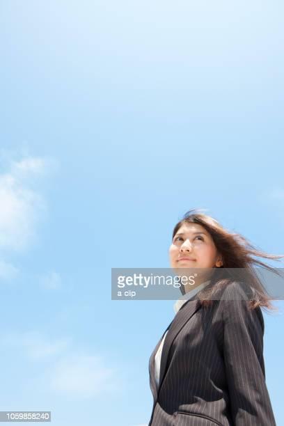 空を見上げるビジネスウーマン - ローアングル ストックフォトと画像