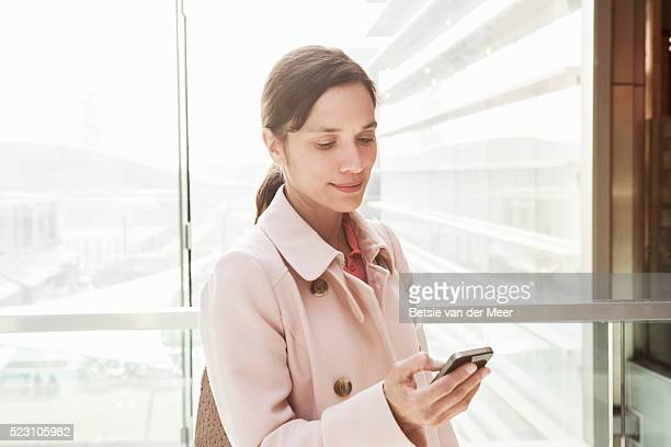 Business woman looks at mobile phone