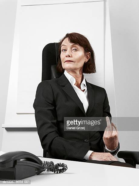 Business woman making hand gesture sitting behind desk, portrait