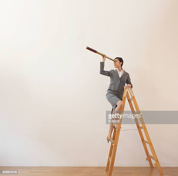 business woman on ladder with telescope