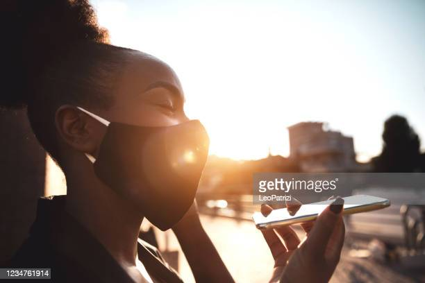 business woman out in the city wearing a protective face mask - speech recognition stock pictures, royalty-free photos & images