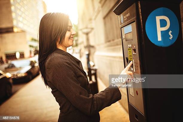 business woman paying th parking at the machine - parking sign stock photos and pictures