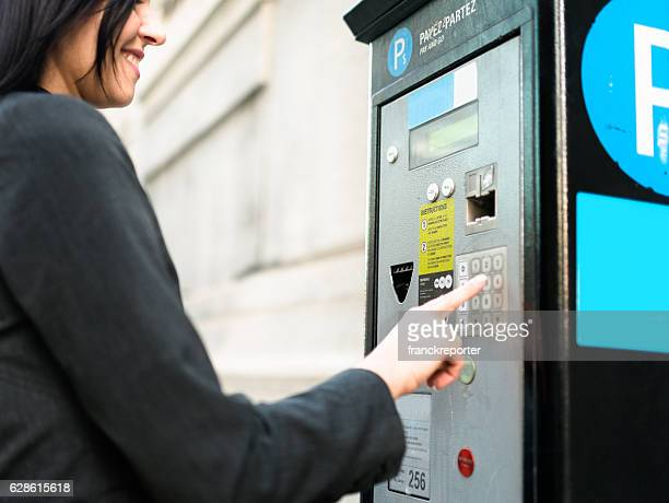 business woman paying th parking at the machine - parking meter stock photos and pictures