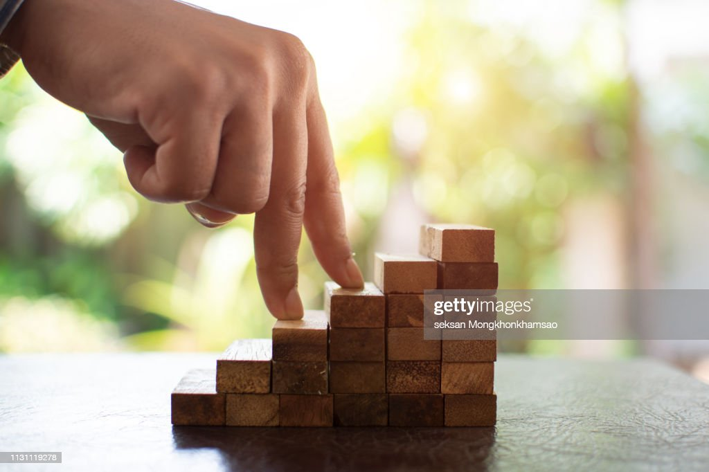 Business Woman Placing Wooden Block On A Tower Concept Risk Control