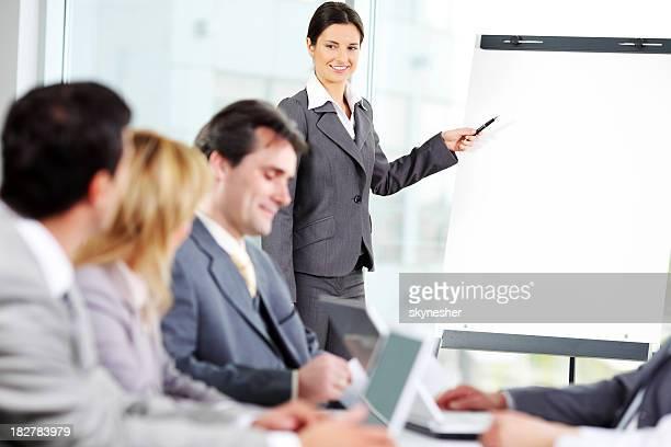 Business Frau zeigt auf das flipchart.