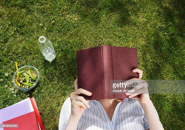 Business woman reading book in park