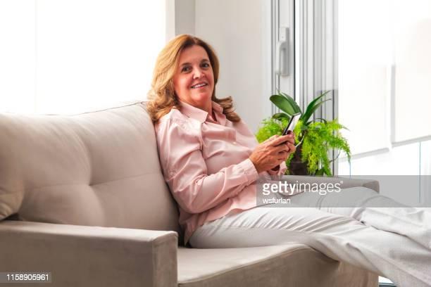 mujer de negocios relajándose en casa. - mujeres de mediana edad fotografías e imágenes de stock
