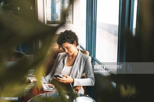 business woman relaxing in the hotel lobby - the media stock pictures, royalty-free photos & images