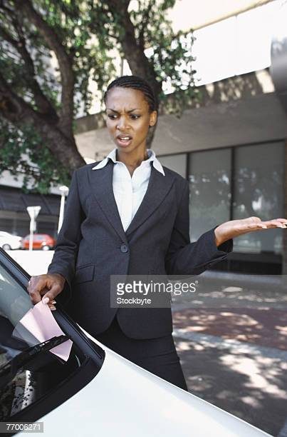 Business woman removing parking ticket from car