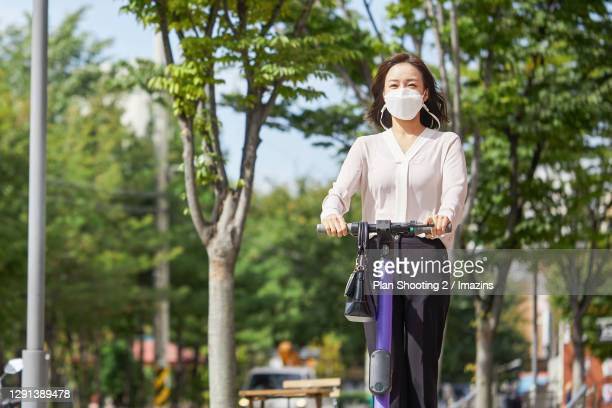 a business woman riding electric scooter while going work - sharing economy stock pictures, royalty-free photos & images