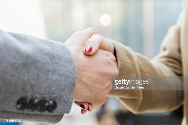 business woman shaking hands with businessman, close-up. - employee engagement stock pictures, royalty-free photos & images