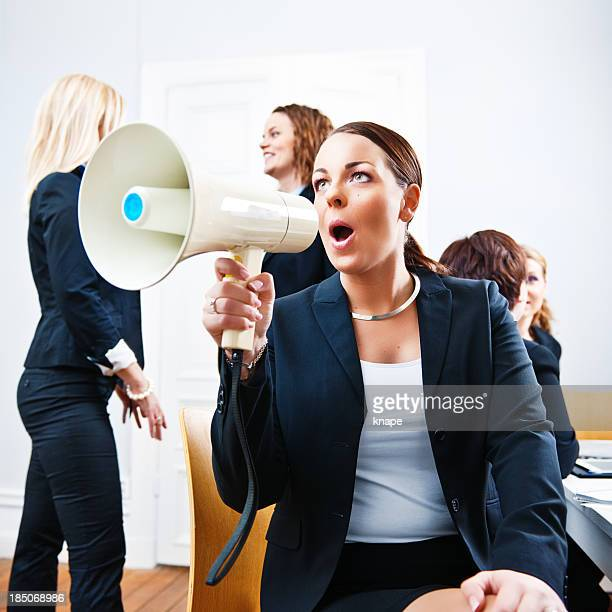 Business woman shouting in a megaphone