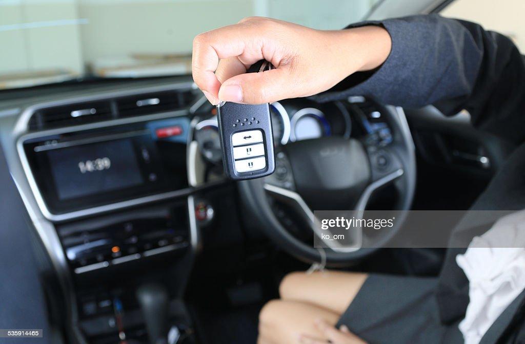 Mujer de negocios mostrar remoto clave en coche moderno de vehículo. : Foto de stock