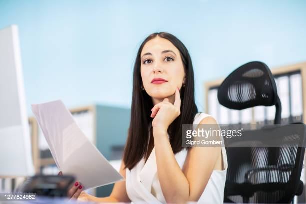 business woman sitting at desk, holding document - sigrid gombert stock pictures, royalty-free photos & images