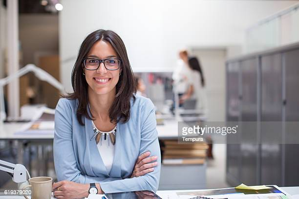 business woman sitting at her desk in corporate office. - directrice photos et images de collection