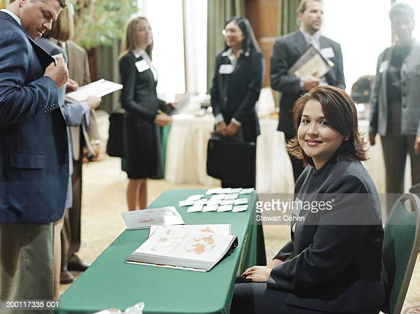 business woman sitting at information table at conference, portrait - tradeshow stock pictures, royalty-free photos & images