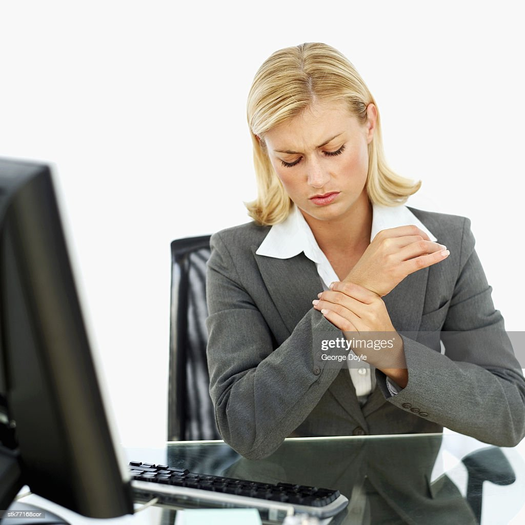 business woman sitting holding her wrist : Stock Photo
