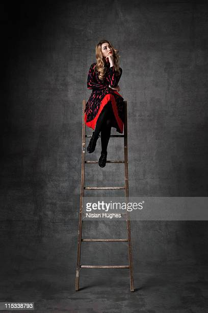 Business woman sitting on ladder