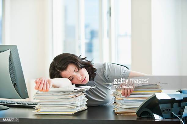 Business woman sleeping on paperwork at desk in office