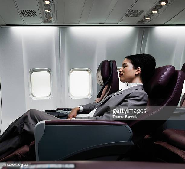 business woman sleeping on plane, side view - business travel stock pictures, royalty-free photos & images