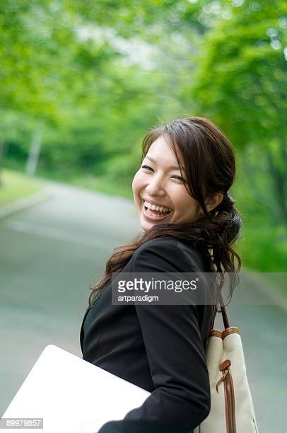 Business woman smiling and holding a laptop