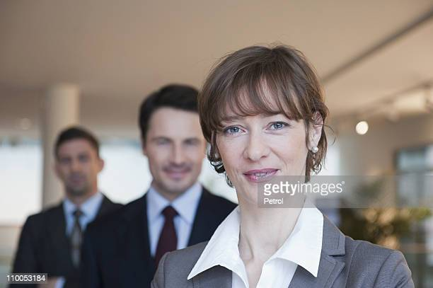 Business woman smiling at camera, two business men behind