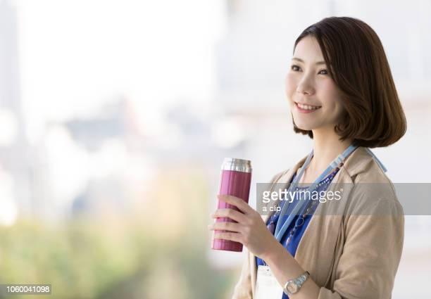 水筒を持っている笑顔のビジネスウーマン - 休憩中 ストックフォトと画像