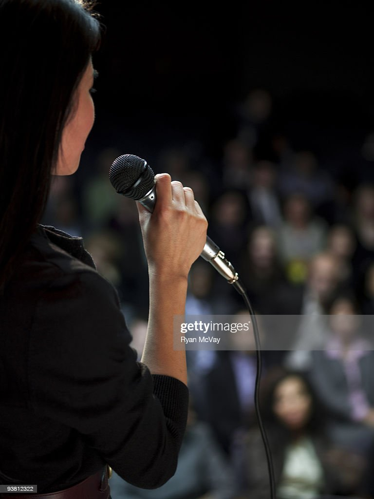 Business woman speaking to crowd : Stock Photo