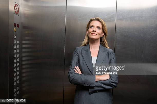 Business woman standing in elevator