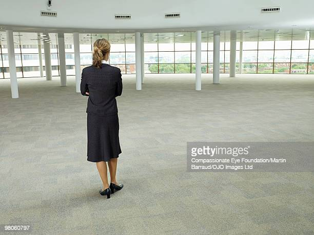 business woman standing in large empty room - 商業不動産 ストックフォトと画像