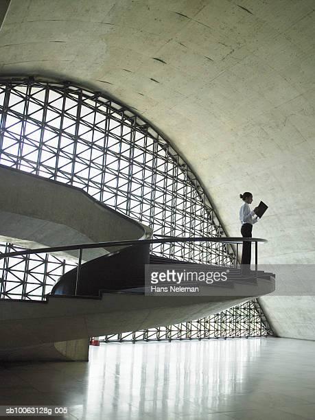 business woman standing on stairs in office - vestimenta de negocios fotografías e imágenes de stock