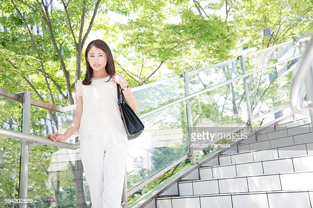 Business woman standing on stairs,smiling